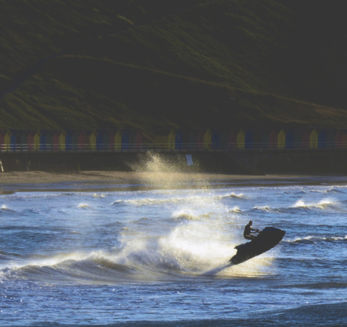 Person using a jet ski in Whitby Bay with beach huts in the distance